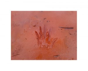 A photo in red mud of a hand print